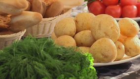 Plate fool of potatoes, plate fool of parsley on a table. Tomatoes and baguete also on a table stock footage