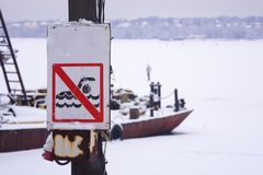 Plate forbidding swimming on a wooden pole. Against the backdrop of a winter river royalty free stock photo