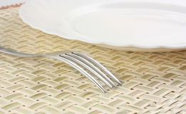 Plate and fork_1. Plate with a fork on a bamboo placemat Stock Images