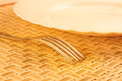 Plate and fork. Plate with a fork on a bamboo placemat Royalty Free Stock Photos