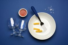 Plate, fork, glasses on the blue table Royalty Free Stock Image