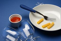 Plate, fork, glasses on the blue table Stock Photography