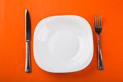 Plate with fork and knife. White plate with fork and knife on paper Royalty Free Stock Photos