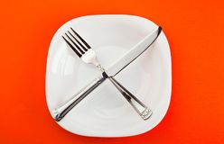 Plate with fork and knife. White plate with fork and knife on paper Royalty Free Stock Photo