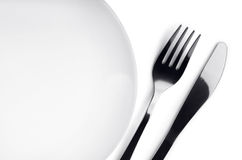 Plate, fork and knife. Empty plate with fork and knife on white background stock image