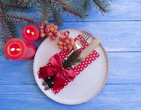 Plate, fork, knife, branch of a Christmas tree beautiful templates , decorative bow on a blue wooden background, candle. Plate, fork, knife, branch of a royalty free stock images