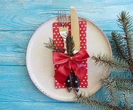 Plate, fork, knife, branch of a Christmas tree beautiful templates , decorative bow on a blue wooden background,. Plate, fork, knife, branch of a Christmas tree royalty free stock images