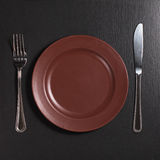 Plate, fork and knife. Brown plate with fork and knife on black stone table, top view royalty free stock images