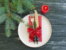 Plate, fork, knife, candle, holiday dining celebration serving branch menu of a Christmas tree on a dark wooden background. Plate, fork knife candle branch of a royalty free stock image