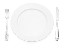 Plate with fork and knife. Empty plate with fork and knife, isolated on white background Royalty Free Stock Photos
