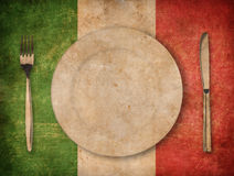 Plate, fork and knife on grunge italian flag background. Plate, fork and knife on grunge italian flag stock image