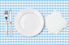 Plate, fork, knife and napkin over blue tableclot Stock Images