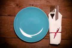 Plate, fork and knife in napkin on wooden background. Toned Royalty Free Stock Photo