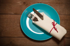 Plate, fork and knife in napkin on wooden background. Toned Royalty Free Stock Photography