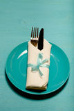 Plate, fork and knife in napkin on wooden background. Toned Stock Photo