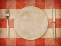 Plate, fork, knife over grunge tablecloth background Stock Photos