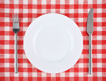 Plate, fork, knife on a red checkered tablecloth. Stock Images