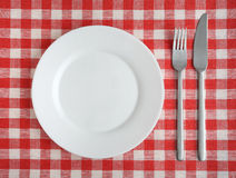 Plate with fork and knife on a red checkered tablecloth. Plate with fork and knife on a red checkered tablecloth Stock Photography