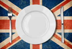 Plate, fork and knife on UK flag Royalty Free Stock Photo