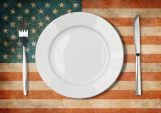 Plate, fork and knife on USA flag Stock Photography