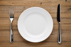Plate, fork and knife on wood Royalty Free Stock Photography