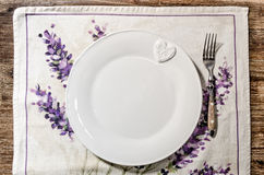 Plate and fork laid on vintage wooden dining table Stock Photography