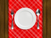 Plate, fork, spoon on a red checkered tablecloth. Lie on a wooden table. realistic style. vector illustration Stock Image