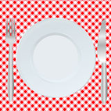 Plate, fork and spoon on  square tablecloth Stock Photo