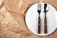 Plate with fork and spoon. White plate with fork and spoon on the craft paper background Stock Photos