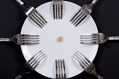 Plate and forks. 8 forks around a plate with a peanut in center Stock Photo