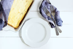 Plate with forks cottage cheese casserole on a white background. Top view, toned image, film effect. White plate with a forks cottage cheese casserole on a white Royalty Free Stock Photo