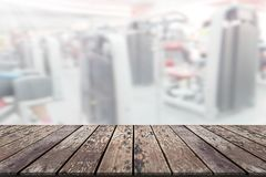 Plate-forme d'espace vide de conseil en bois avec des equipmen de gymnase de forme physique de tache floue photo stock