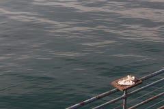 Plate-forme de découpage de poissons sur la balustrade d'un pilier avec la serviette et les couteaux, mer calme, l'espace de copi photo stock