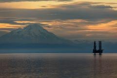 Plate-forme de pétrole et de gaz dans le cuisinier Inlet avec la montagne couronnée de neige Photo libre de droits