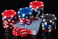 Plate-forme des cartes et des jetons de poker avec des cubes sur un fond réfléchi foncé Image stock