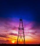Plate-forme pétrolière profilée sur le ciel excessif de coucher du soleil photographie stock