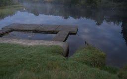 Plate-forme sur un lac à l'aube Photos stock