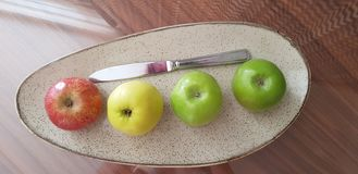 Four apples of various colors and a knife stay on glass table stock photo