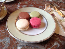 Macaroons. A plate of four Macaroons, pink, green, white and chocolate from Laduree  Restaurant in Paris, France Stock Photos