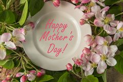Plate framed with blossoming apple branches and text Happy Mothe. R`s Day Stock Photo
