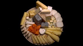 A plate of French cheeses. On a black background stock video