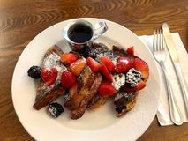 Plate of French Toast fruit and syrup. Breakfast, French Toast with strawberries and boysenberries on a white plate, wood table, utensils to the side Royalty Free Stock Images