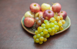 Plate with fresh autumnal fruits. grapes in selective focus Stock Image