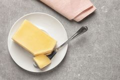 Plate with fresh butter and knife on table, top view. Space for text stock photo