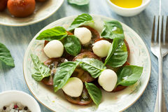 Plate of fresh caprese salad with black tomatoes, mini mozzarella and basil leaves Royalty Free Stock Photography