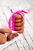 Plate of fresh chocolate cookies with pink ribbon and confetti Stock Photos