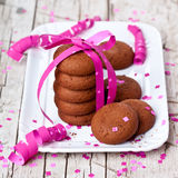 Plate of fresh chocolate cookies with pink ribbon and confetti Stock Image