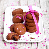 Plate of fresh chocolate cookies with pink ribbon and confetti Royalty Free Stock Images