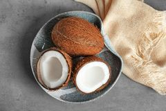 Plate with fresh coconuts. On grey background Royalty Free Stock Photos
