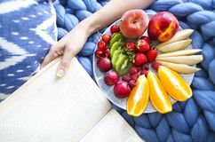 Plate with fresh fruit salad on a blue plaid with book. Plate with fresh fruit salad on a blue plaid and book. Woman reading the book and eating fresh fruits Royalty Free Stock Photos